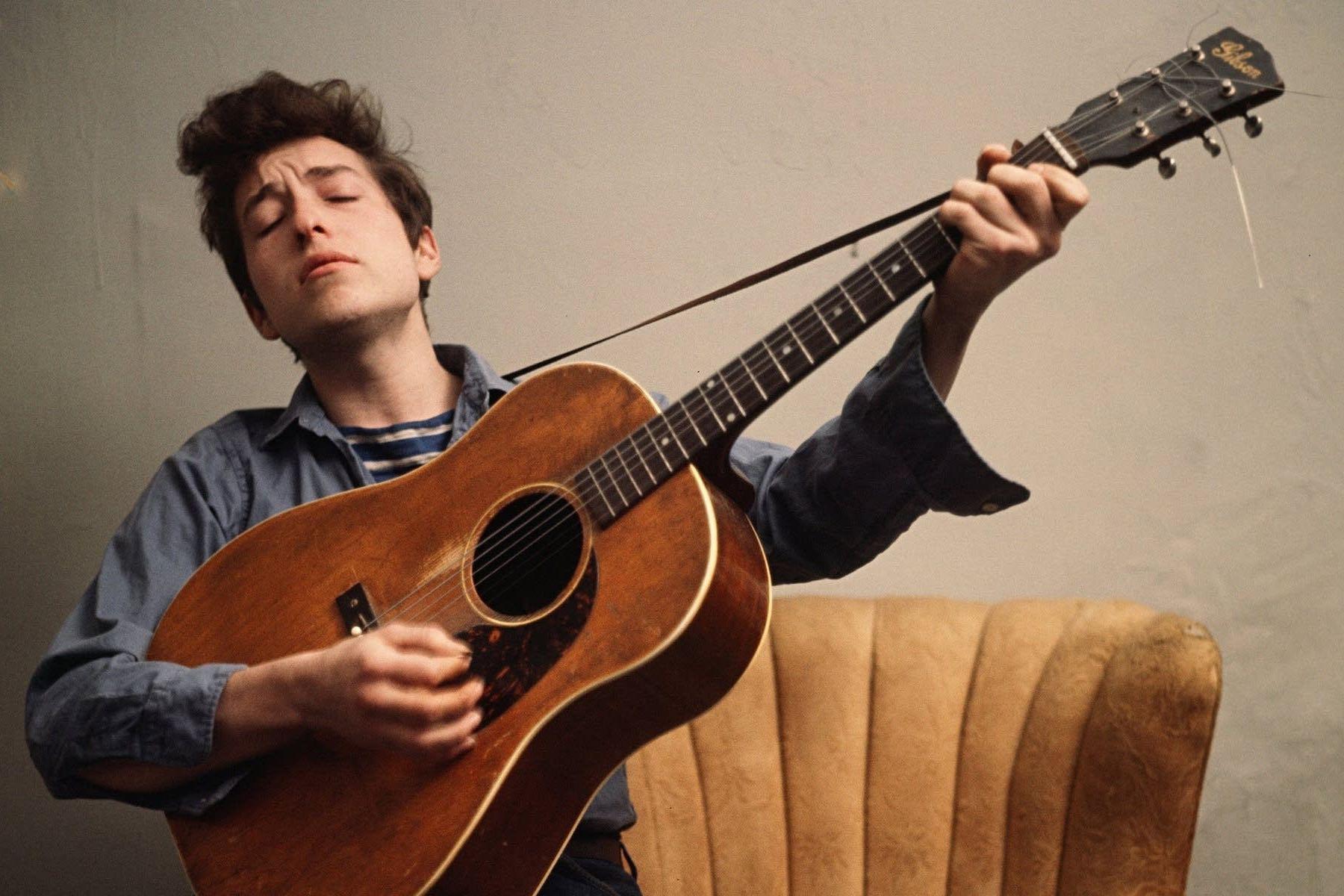 Bob Dylan playing a guitar